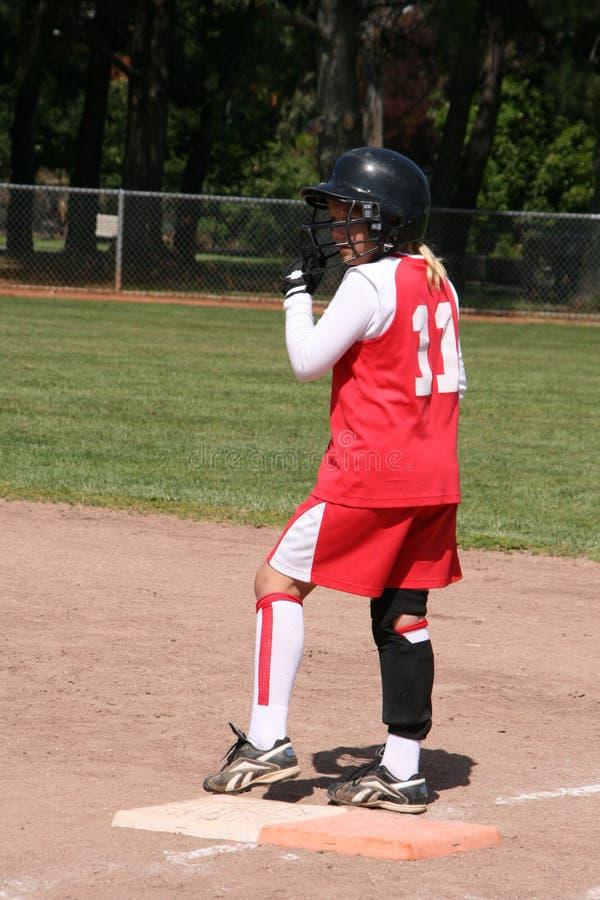 Jugador de beísbol con pelota blanda en base fotos de archivo