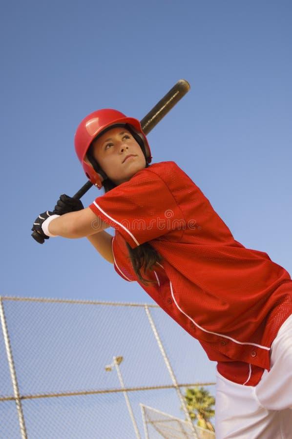 Jugador de beísbol con pelota blanda en el palo imagen de archivo