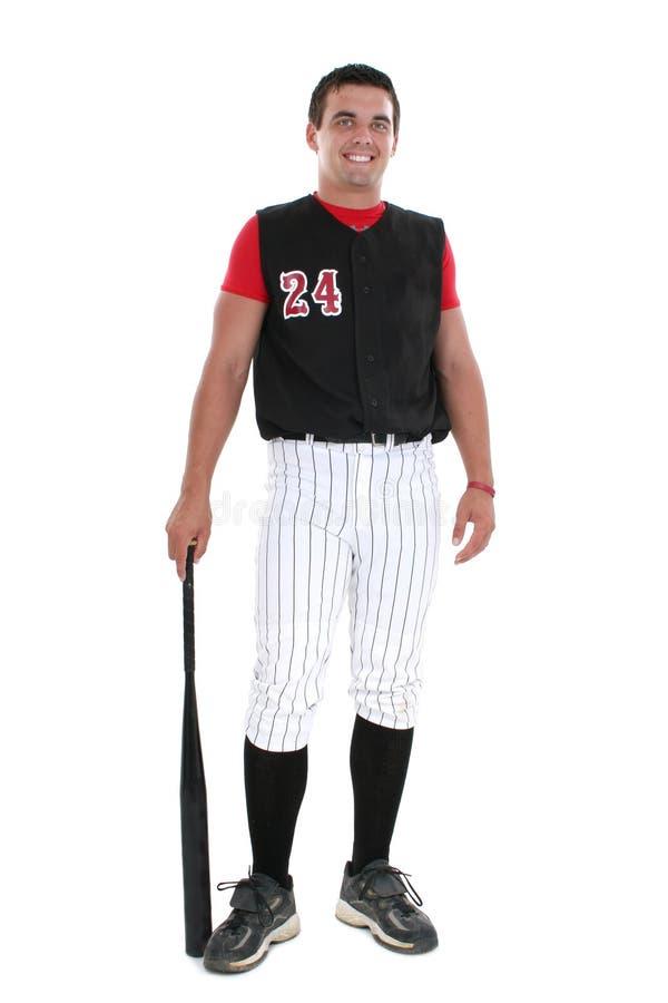 Jugador de beísbol con pelota blanda en uniforme con el palo fotografía de archivo