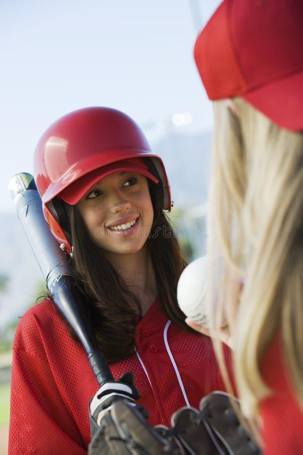 Jugador de beísbol con pelota blanda femenino que habla con el teamma foto de archivo libre de regalías