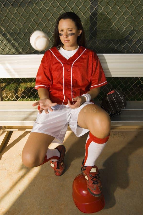 Jugador de beísbol con pelota blanda que se sienta en bola que lanza del banco fotografía de archivo libre de regalías