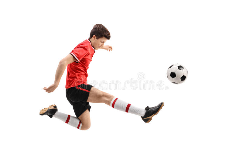 Jugador de fútbol adolescente que golpea un fútbol con el pie foto de archivo