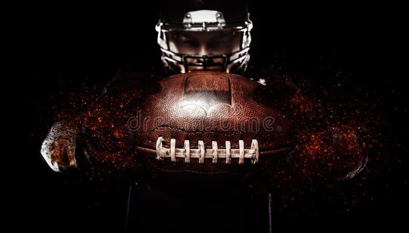 Jugador de fútbol americano, atleta en casco con la bola en fondo negro Papel pintado del deporte con el copyspace foto de archivo