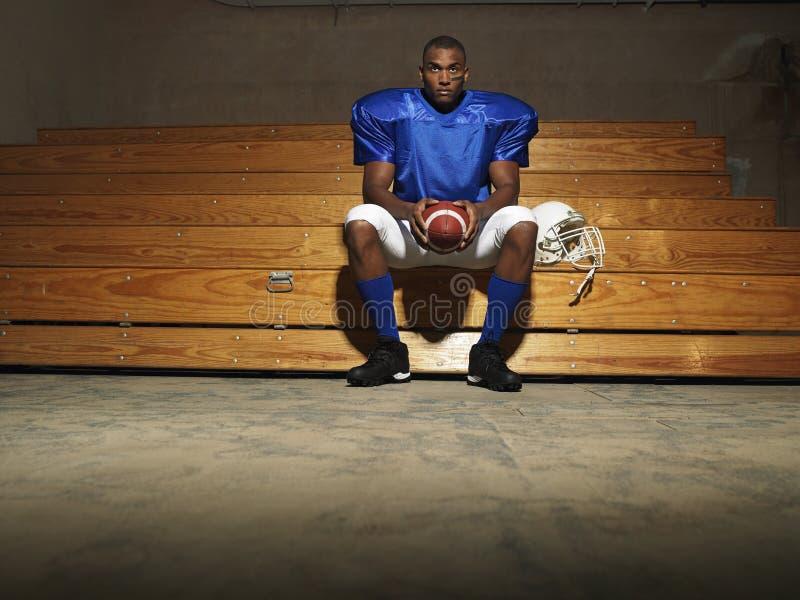 Jugador de fútbol americano con la bola en banco fotos de archivo libres de regalías