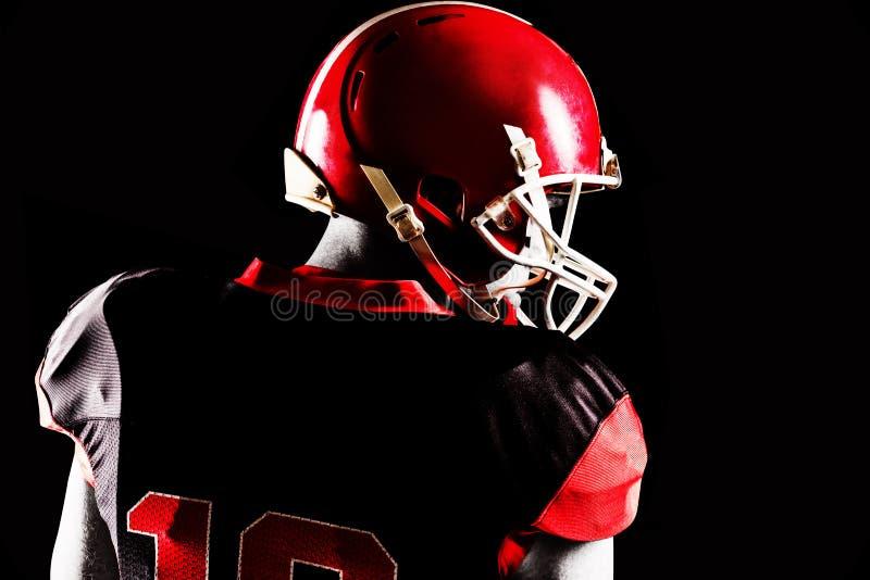 Jugador de fútbol americano en el casco que mira apagado al lado fotografía de archivo