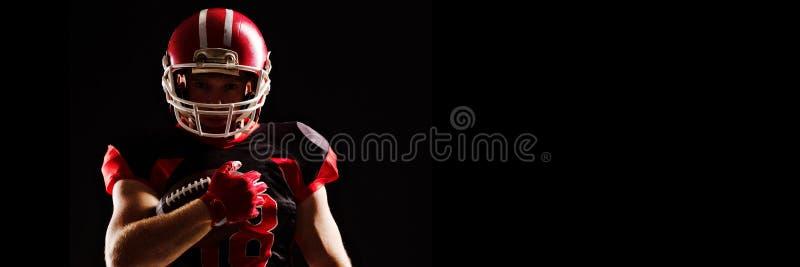 Jugador de fútbol americano en el casco que sostiene la bola de rugbi imagen de archivo libre de regalías