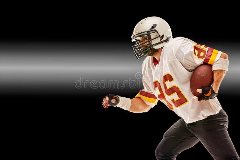 Jugador de fútbol americano en el movimiento con la bola en un fondo negro con una línea ligera, espacio de la copia El concepto  foto de archivo