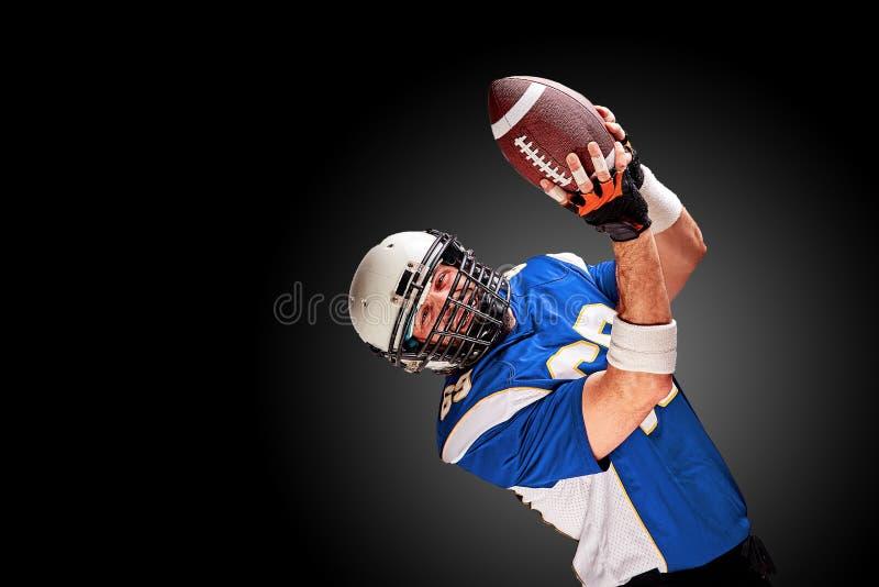 Jugador de fútbol americano en el movimiento con la bola en un fondo negro con una línea ligera, espacio de la copia El concepto  fotos de archivo