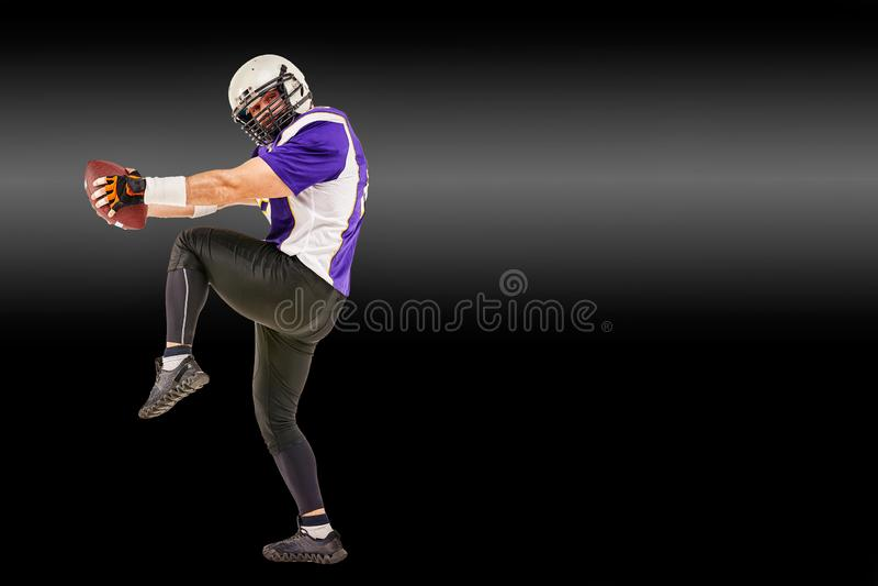 Jugador de fútbol americano en el movimiento con la bola en un fondo negro con una línea ligera, espacio de la copia El concepto  fotografía de archivo