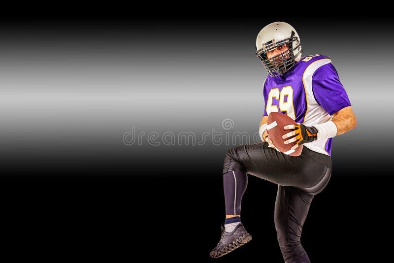 Jugador de fútbol americano en el movimiento con la bola en un fondo negro con una línea ligera, espacio de la copia El concepto  imagen de archivo libre de regalías