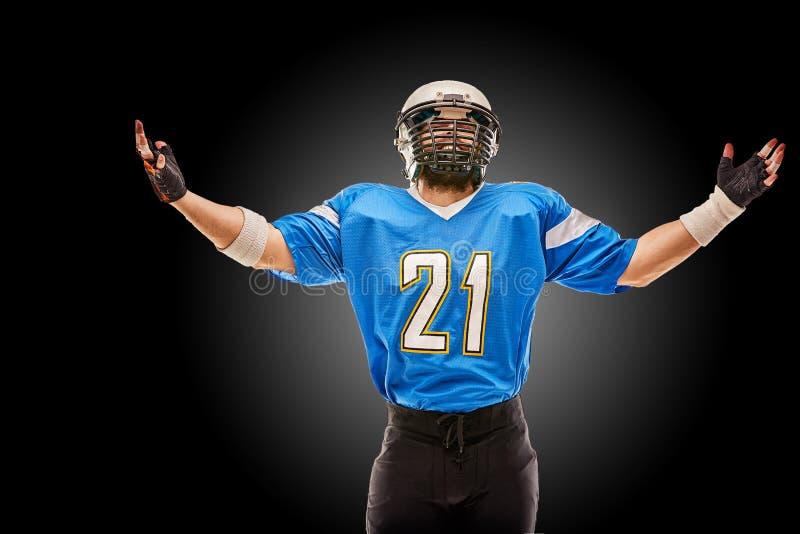 Jugador de fútbol americano en las actitudes uniformes para la cámara Un atleta hermoso en uniforme en un fondo negro con a fotos de archivo
