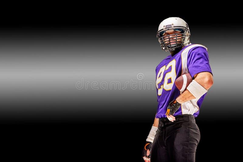 Jugador de fútbol americano en las actitudes uniformes para la cámara Un atleta hermoso en uniforme en un fondo negro con a imagenes de archivo