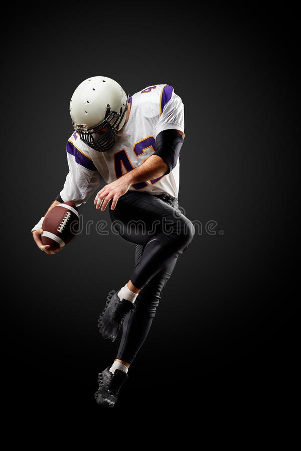 Jugador de fútbol americano en un salto con una bola en un fondo negro imagenes de archivo