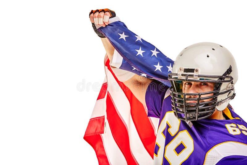 Jugador de fútbol americano patriótico que presenta en la cámara en el fondo blanco con la bandera de los E.E.U.U. El concepto de imágenes de archivo libres de regalías