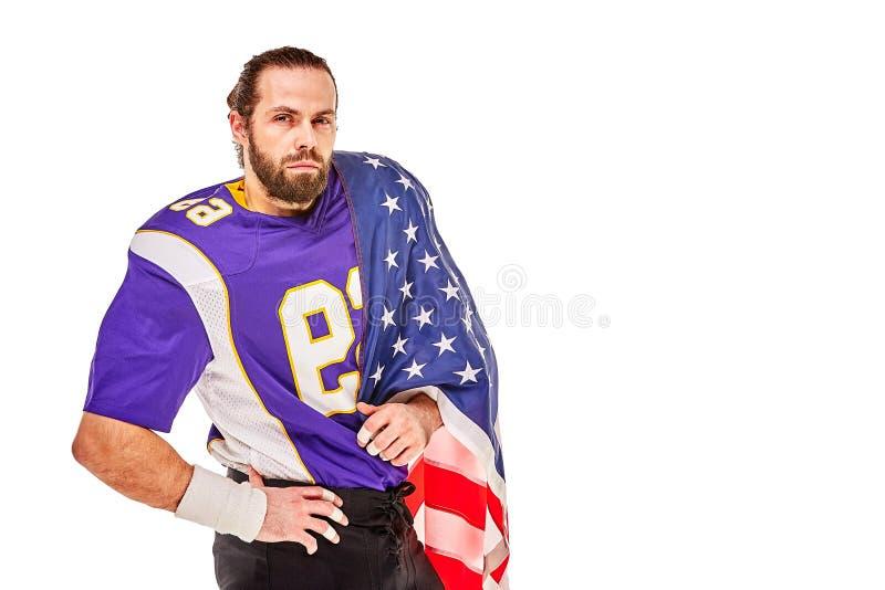 Jugador de fútbol americano patriótico que presenta en la cámara en el fondo blanco con la bandera de los E.E.U.U. El concepto de foto de archivo