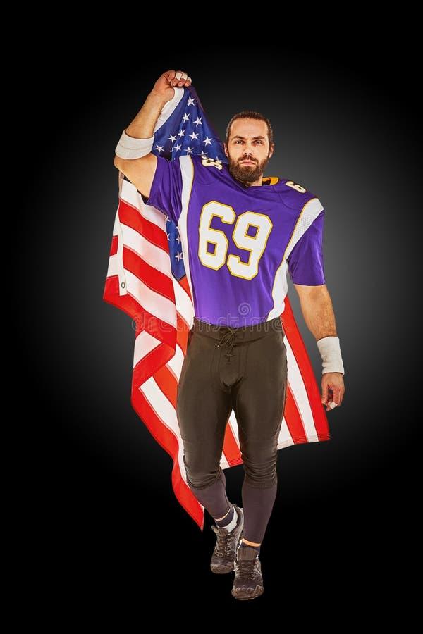 Jugador de fútbol americano patriótico que presenta en la cámara en fondo negro con la bandera de los E.E.U.U. El concepto de pat imagen de archivo libre de regalías