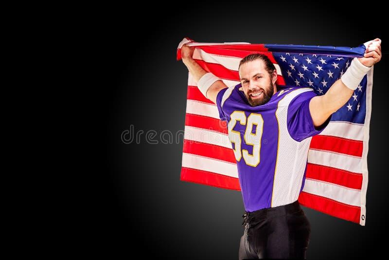Jugador de fútbol americano patriótico que presenta en la cámara en fondo negro con la bandera de los E.E.U.U. El concepto de pat foto de archivo libre de regalías