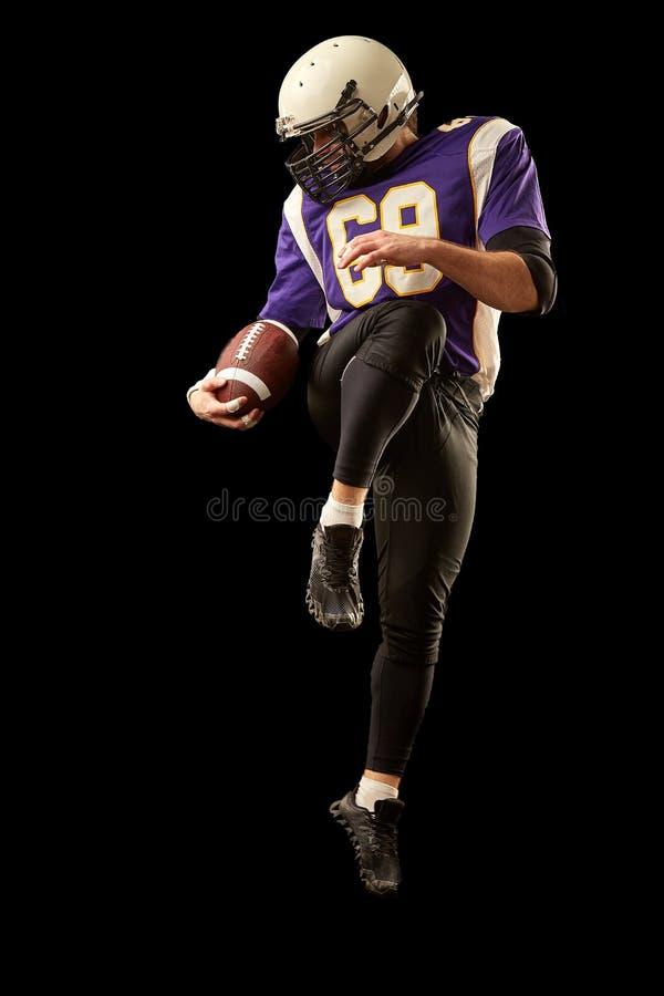 Jugador de fútbol americano que celebra una bola mientras que salta lejos de una huelga fondo negro, espacio de la copia Violeta  fotos de archivo