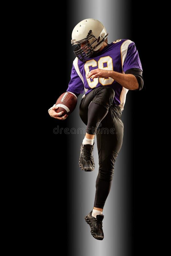 Jugador de fútbol americano que celebra una bola mientras que salta lejos de una huelga fondo negro, espacio de la copia Violeta  fotografía de archivo