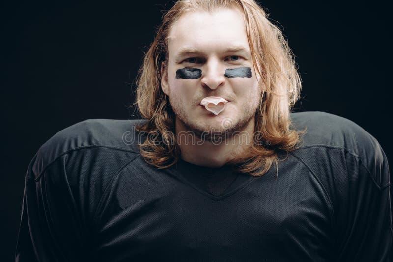 Jugador de fútbol americano resuelto que presenta con la cara y el chicle pintados foto de archivo