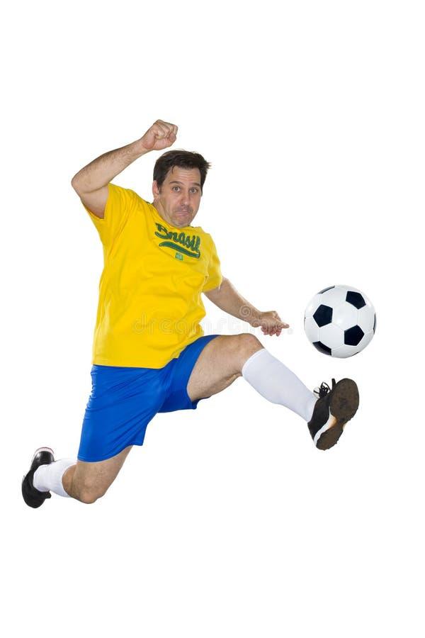 Jugador de fútbol brasileño, saltando, amarillo y azul. imagen de archivo libre de regalías