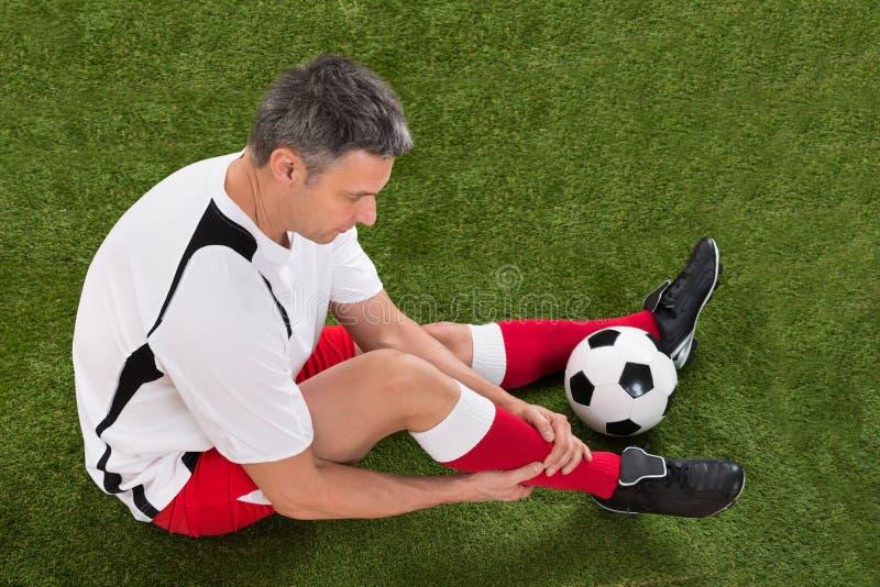 Jugador de fútbol con lesión en pierna foto de archivo libre de regalías