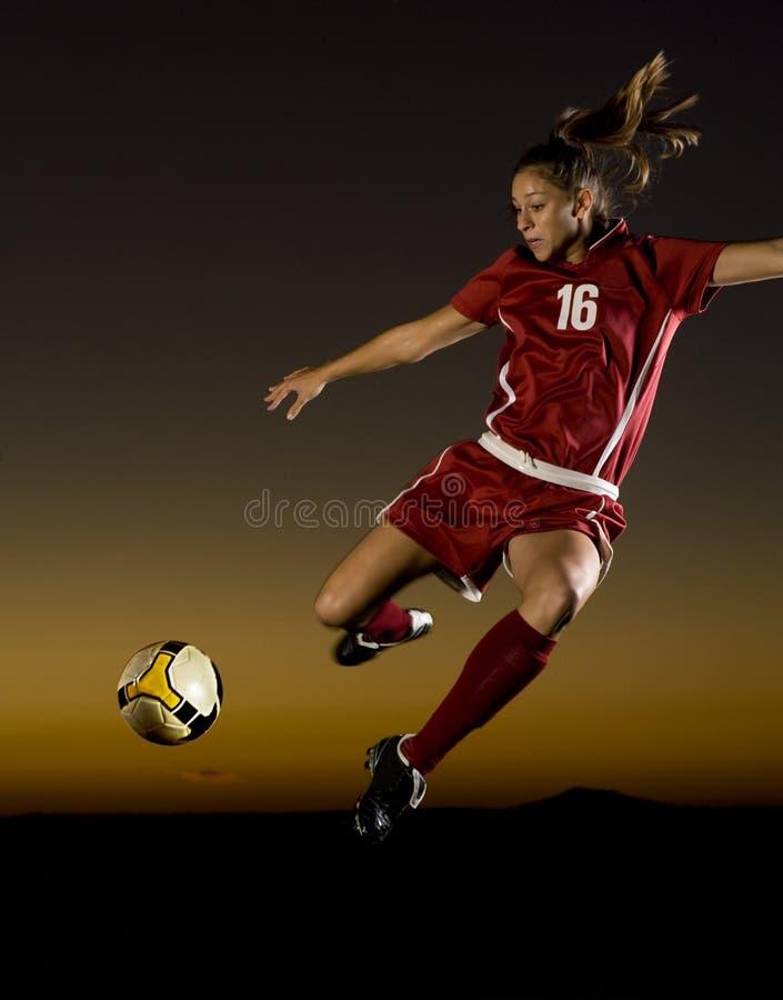 Jugador de fútbol de sexo femenino alrededor para golpear la bola con el pie imagen de archivo