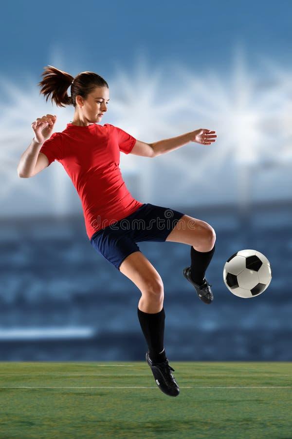 Jugador de fútbol de sexo femenino que golpea la bola con el pie foto de archivo libre de regalías