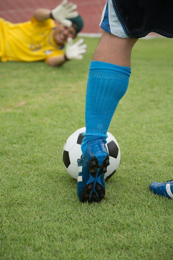 Jugador de fútbol del ataque que tira al equipo de defensa imagen de archivo libre de regalías