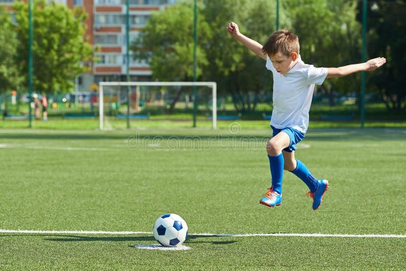 Jugador de fútbol del muchacho con salto antes del retroceso en bola fotos de archivo