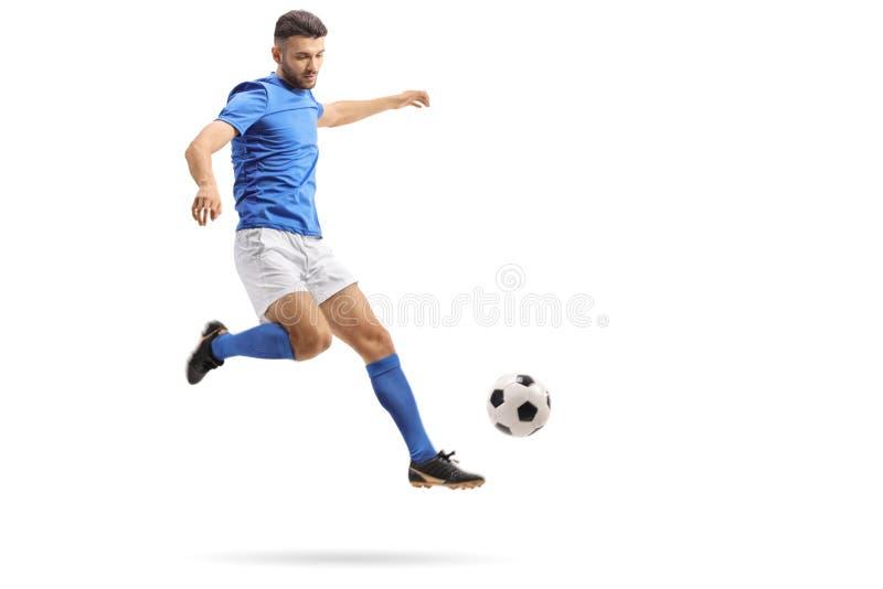 Jugador de fútbol en el mediados de-aire que golpea un fútbol con el pie imagen de archivo