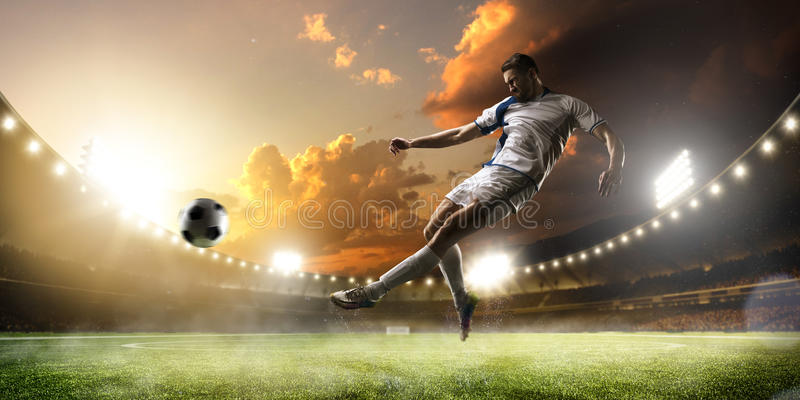 Jugador de fútbol en la acción en fondo del panorama del estadio de la puesta del sol imagenes de archivo