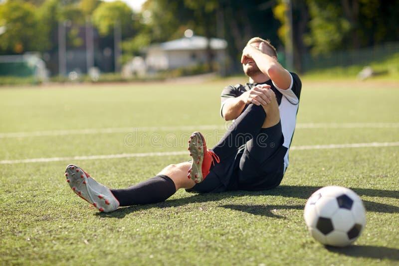 Jugador de fútbol herido con la bola en campo de fútbol imagen de archivo