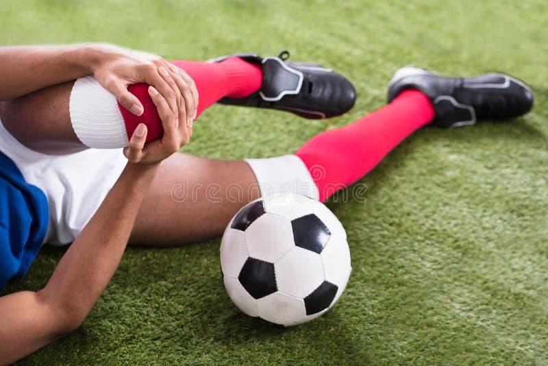 Jugador de fútbol herido en campo foto de archivo libre de regalías