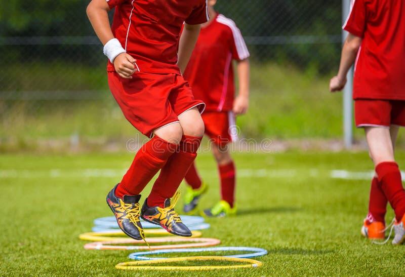 Jugador de fútbol joven que practica en la echada Fútbol Equpment del fútbol Práctica de salto dinámica del fútbol fotografía de archivo