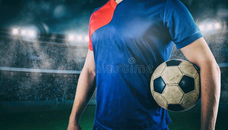Jugador de fútbol listo para jugar con la bola en sus manos en el estadio foto de archivo