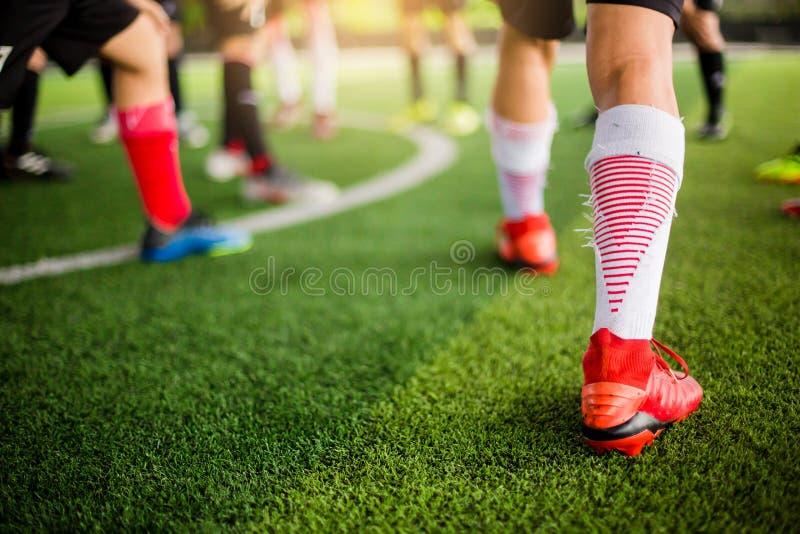 Jugador de fútbol que activa en césped artificial verde y que estira sus pies calentamiento del cuerpo y del pie foto de archivo libre de regalías