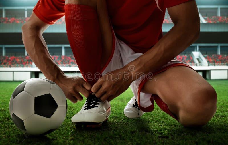 Jugador de fútbol que ata los zapatos en el campo fotografía de archivo