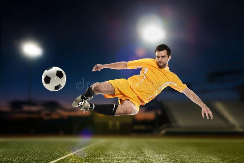 Jugador de fútbol que golpea la bola con el pie fotos de archivo
