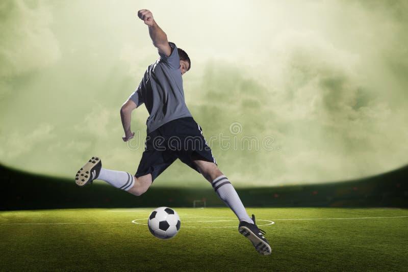 Jugador de fútbol que golpea la bola con el pie en un estadio, cielo verde con las nubes foto de archivo