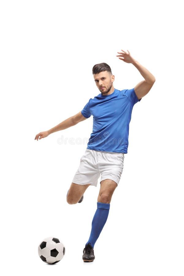 Jugador de fútbol que golpea un fútbol con el pie foto de archivo libre de regalías