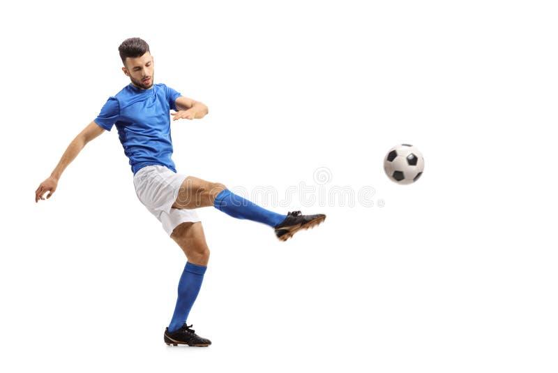 Jugador de fútbol que golpea un fútbol con el pie fotografía de archivo libre de regalías