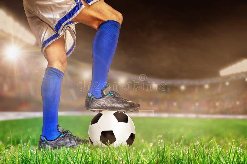 Jugador de fútbol que se coloca sobre fútbol en estadio al aire libre con el poli fotos de archivo