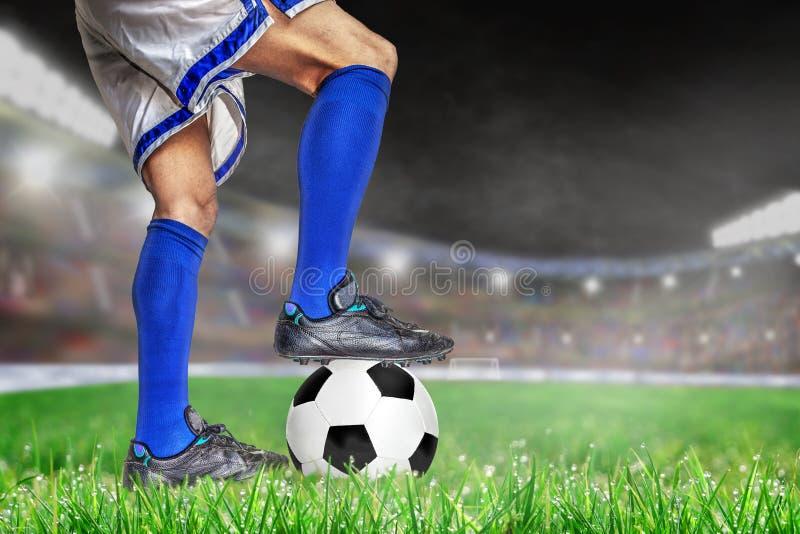 Jugador de fútbol que se coloca sobre fútbol en estadio al aire libre con el poli foto de archivo libre de regalías