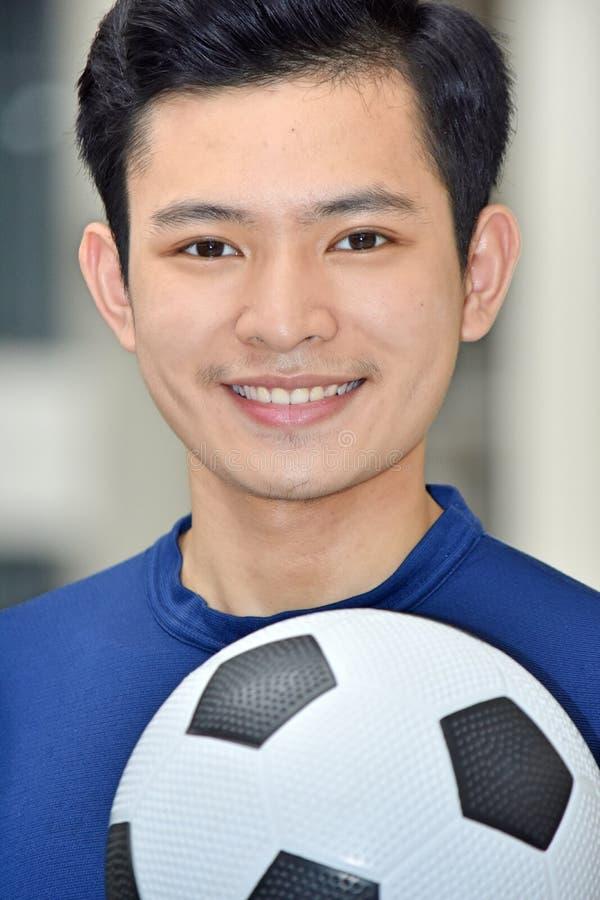 Jugador de fútbol de sexo masculino deportivo sonriente con el balón de fútbol imágenes de archivo libres de regalías