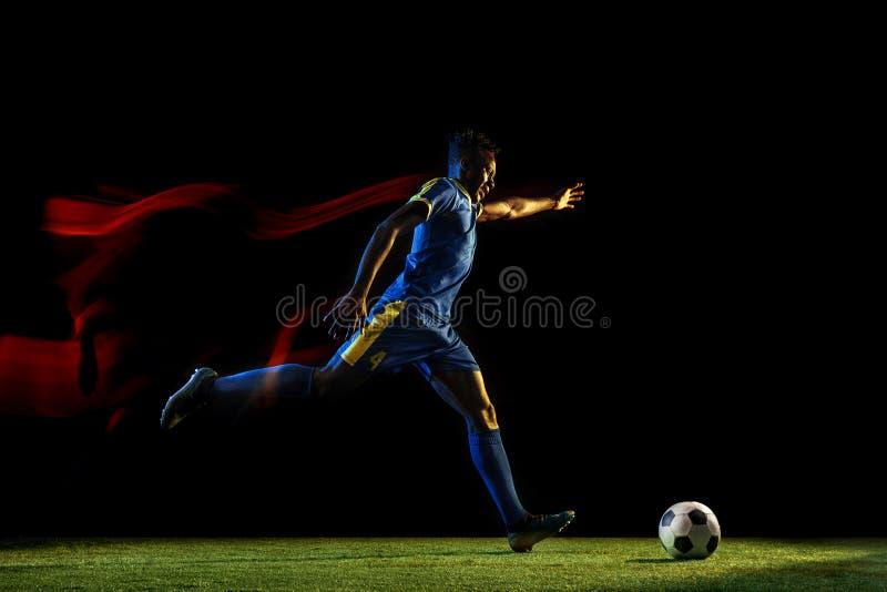 Jugador de fútbol de sexo masculino que golpea la bola con el pie en fondo oscuro en luz mezclada foto de archivo libre de regalías