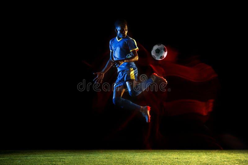 Jugador de fútbol de sexo masculino que golpea la bola con el pie en fondo oscuro en luz mezclada fotografía de archivo
