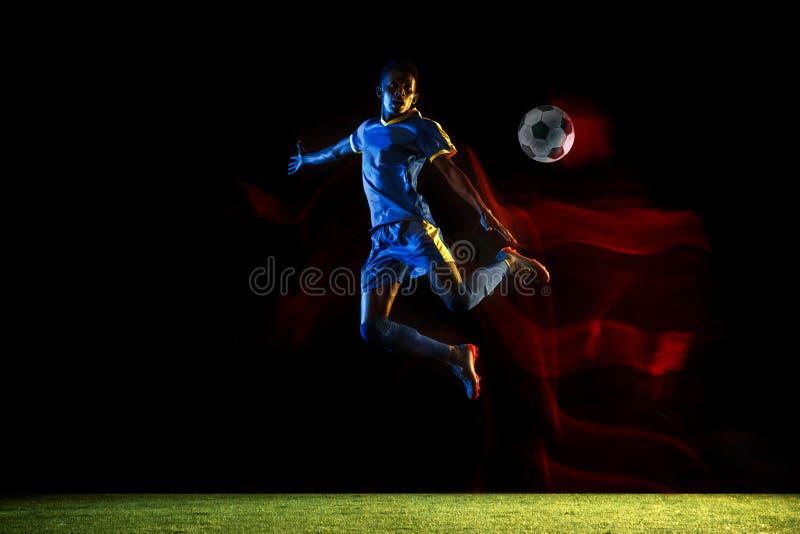Jugador de fútbol de sexo masculino que golpea la bola con el pie en fondo oscuro en luz mezclada fotografía de archivo libre de regalías