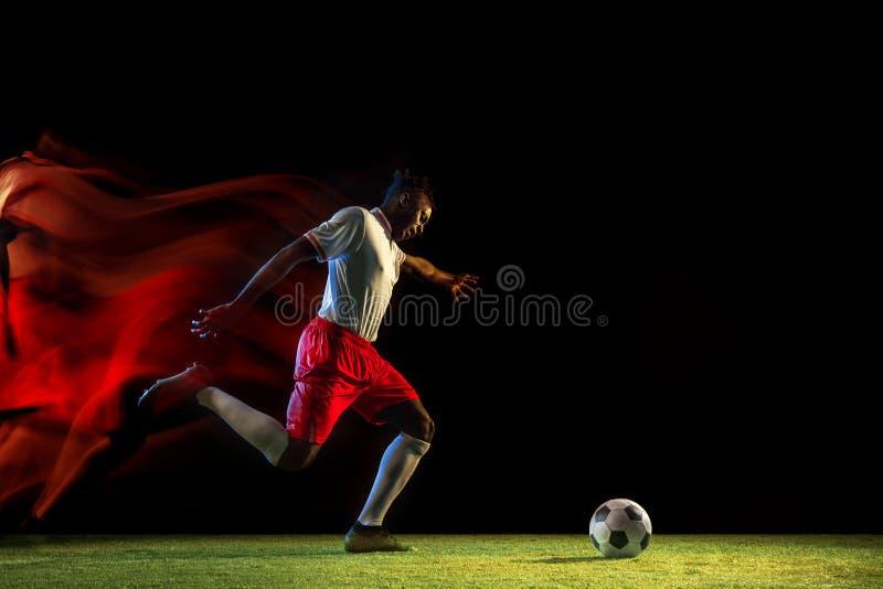 Jugador de fútbol de sexo masculino que golpea la bola con el pie en fondo oscuro en luz mezclada fotos de archivo