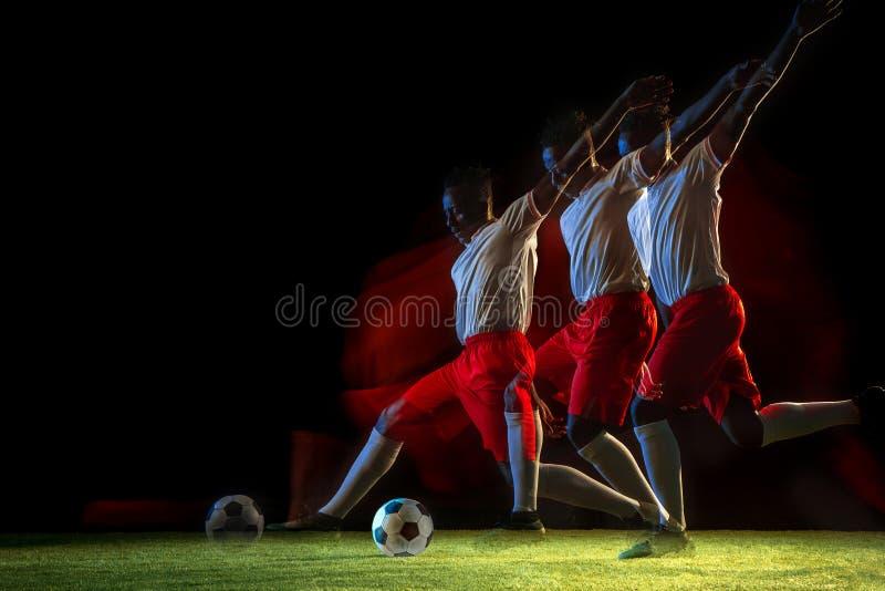 Jugador de fútbol de sexo masculino que golpea la bola con el pie en fondo oscuro en luz mezclada imagen de archivo libre de regalías